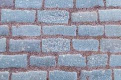 Rij van steen rechthoekige grijze tegels met het zandpatroon van het terracotta bruin grint royalty-vrije stock afbeeldingen