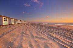 Rij van strandhutten bij zonsondergang, Texel, Nederland Stock Afbeelding