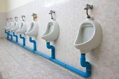 Rij van vier urinoirs Stock Fotografie