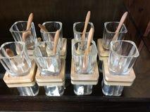 Rij van vierkante glazen met houten onderlegger voor glazen Stock Fotografie