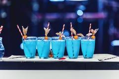 Rij van vijf blauwe cocktails met ijs en buizen, achterlichten Royalty-vrije Stock Foto's