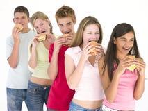 Rij van vijf vrienden die hamburgers eten Stock Foto's