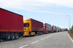 Rij van vrachtwagens de internationale grens overgaan, rode en verschillende kleurenvrachtwagens die in opstopping op de weg stock foto