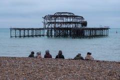 Rij van vrouwen die op bekiezeld strand in Brighton het UK op een winterse middag in December, voor de ruïnes van het Westenpijle royalty-vrije stock foto's