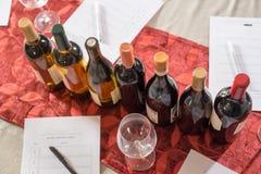 Rij van Wijnflessen met Glazen en Proevende Vormen Stock Afbeeldingen