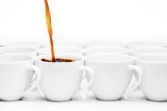 Rij van witte koffiekoppen, één die met koffie worden gevuld Stock Foto's