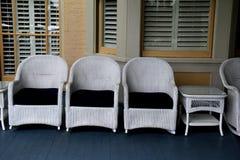 Witte Rieten Stoel : Rij van witte rieten stoelen en lijsten aangaande voorportiek stock