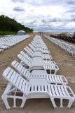 Rij van witte stoelen voor het zonnebaden op het zandige strand Stock Foto