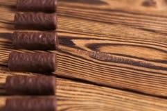 Rij van yummy chocoladesuikergoed op oude doorstane houten lijst stock foto