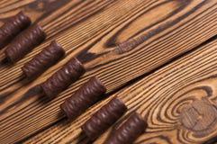 Rij van yummy chocoladesuikergoed op oude doorstane houten lijst stock foto's