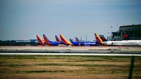 Rij van Zuidwesten en Delta Airlines-vliegtuigen bij hun poorten wordt geparkeerd die stock afbeelding