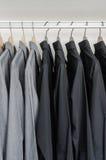 Rij van zwarte en grijze overhemden die op kleerhanger hangen Stock Fotografie
