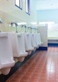 Rij witte urinoirs in de badkamers van mensen Stock Afbeelding