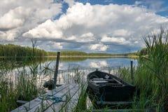 Rijboot aan een pijler in een glazig meer in Zweden wordt gebonden dat royalty-vrije stock fotografie