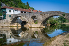 Rijeka Crnojevica old bridge panoraic view with reflections on the calm river waters. Stock Photography