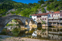 Rijeka Crnojevica old town and bridge. Rijeka Crnojevica village houses near the river water and old stone bridge. Popular riviera resort in Montenegro Royalty Free Stock Photos