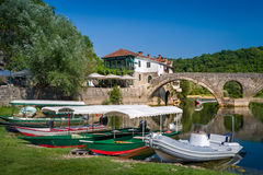 Rijeka Crnojevica old town excursion boats moored. Ancient arch bridge at background. Starting point of boat trips to Skadar lake national park, Montenegro Royalty Free Stock Photos
