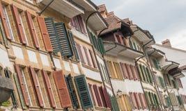 Rijen op rijen van oude huisvoorzijden met mooie vensters en houten blinden in vele verschillende kleuren Stock Afbeeldingen
