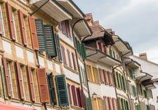 Rijen op rijen van oude huisvoorzijden met mooie vensters en houten blinden in vele verschillende kleuren Royalty-vrije Stock Fotografie