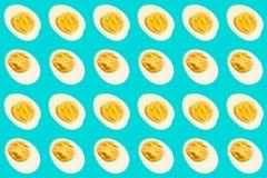 Rijen van de vele helften gekookte eieren op een blauwe achtergrond vector illustratie