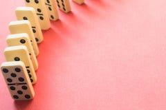 Rijen van Domino's van hierboven op roze stock afbeeldingen