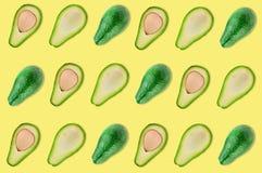 Rijen van geheel en de helften van organische avocado met en zonder pitten in centrum van gele lijst in keuken of markt stock fotografie