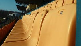 Rijen van genummerde plastic stoelen in open voetbalstadion stock videobeelden