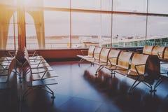 Rijen van houten zetels dichtbij luchthavenpoort Stock Foto