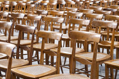 Rijen van lege houten en rieten stoelen Stock Afbeeldingen