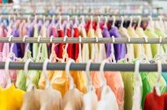 Rijen van kleurrijke kleren op hangers bij winkel. Stock Afbeeldingen
