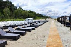 Rijen van stoelen voor het zonnebaden op het zandige strand na regen Stock Foto