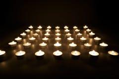 Rijen van votive kaarsen die in de duisternis branden stock foto's