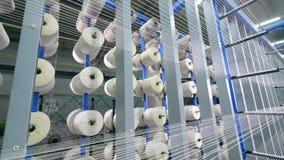 Rijen van witte koorden die op spoelen bij een textielinstallatie rollen stock video