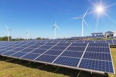 Rijenserie van polycrystalline siliciumzonnepanelen en windturbines die elektriciteit in de hybride post van elektrische centrale Stock Foto's