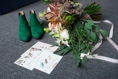 Rijk groen huwelijksboeket met roze linten op de grijze achtergrond Groene bruids schoenen, en huwelijk het vleiende liggen dicht Stock Afbeeldingen