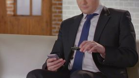 Rijk zakenman het typen aantal van creditcard op het telefoonscherm, online bankwezen stock footage