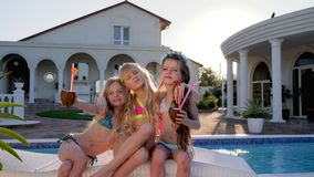 Rijke kinderen die voor camera in achtergrondpool, kinderenberoemdheden op de zomervakantie, jonge geitjespartij met cocktails st stock videobeelden