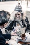 Rijke man die aan handeling van liefdadigheid deelnemen terwijl het overhandigen van geld aan daklozen stock afbeelding
