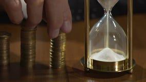 Rijke man die muntstukken op stapels, mening op sandglass zetten die tijd, financiën meten stock videobeelden