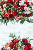 Rijke rode boeketten van rozen, pioenen en ranunculus in het glas Royalty-vrije Stock Foto's
