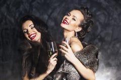 Rijke vrouwen die met kristal van champagne lachen Stock Afbeeldingen