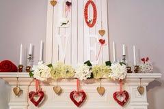 Rijke witte die open haard met rode harten wordt verfraaid stock fotografie