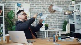 Rijke zakenman die geld werpen die hebbend pret in bureauruimte lachen stock video