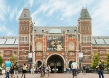 Rijksmuseum building facade with tourists and cyclists in Amsterdam. Amsterdam, Netherlands - August 23, 2018: Rijksmuseum building facade with tourists and royalty free stock photo