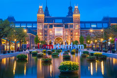 Rijksmuseum building famous landmark in Amsterdam. Blue hour dusk evening illumination with tulip flowers in vases in pools stock photos