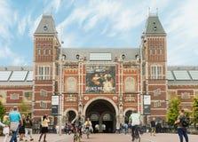 Rijksmuseum byggnadsfasad med turister och cyklister i Amsterdam royaltyfri foto