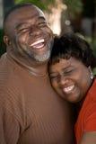 Rijp Afrikaans Amerikaans en paar die lachen koesteren royalty-vrije stock fotografie
