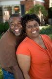 Rijp Afrikaans Amerikaans en paar die lachen koesteren stock afbeeldingen