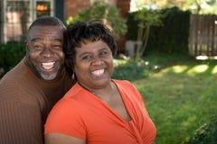 Rijp Afrikaans Amerikaans en paar die lachen koesteren stock foto's