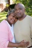 Rijp Afrikaans Amerikaans en paar die lachen koesteren stock foto